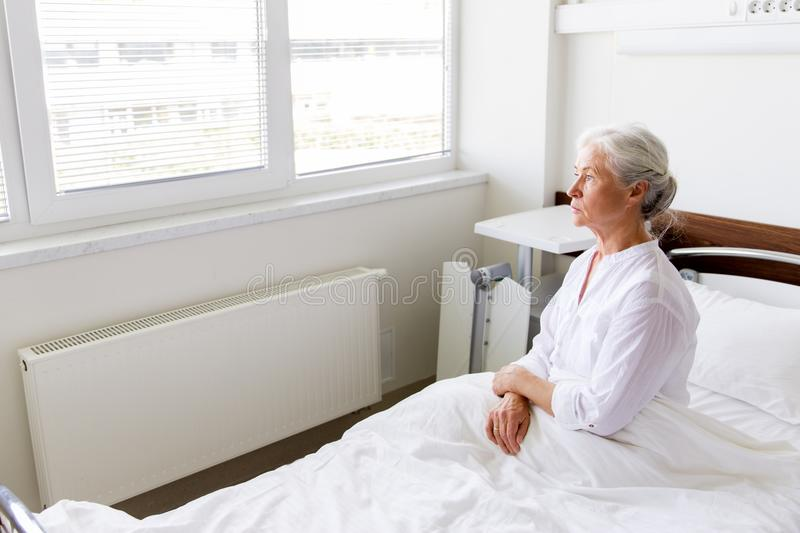 Sad senior woman sitting on bed at hospital ward. Medicine, healthcare and old people concept - sad senior woman sitting on bed at hospital ward stock images