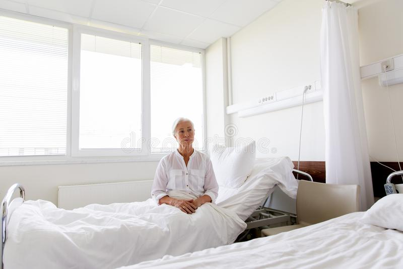 Sad senior woman sitting on bed at hospital ward. Medicine, healthcare and old people concept - sad senior woman sitting on bed at hospital ward stock photo