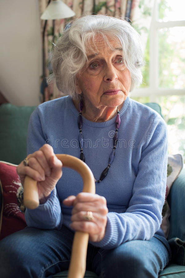 Sad Senior Woman Sitting In Chair Holding Walking Cane. Sad Senior Woman Sits In Chair Holding Walking Cane stock photos