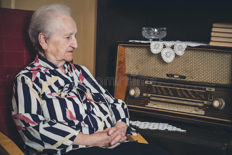 Sad senior woman sitting in a chair stock images
