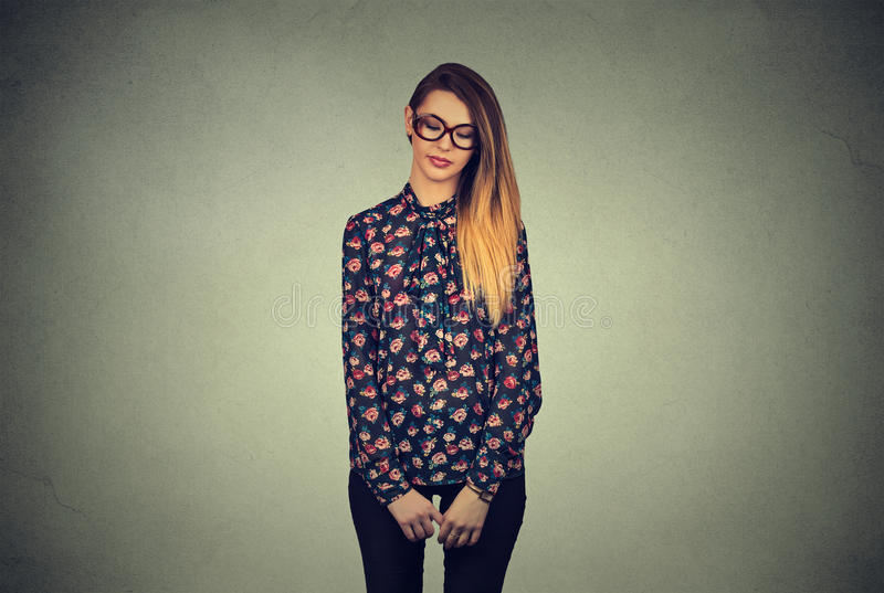 Sad shy insecure woman in glasses looking down avoiding eye contact. Sad shy insecure young woman in glasses looking down avoiding eye contact standing isolated stock images