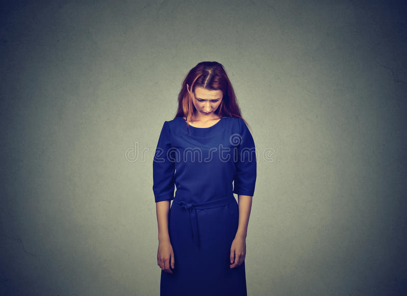 Sad shy insecure young woman standing looking down. Avoiding eye contact isolated on gray wall background royalty free stock photos
