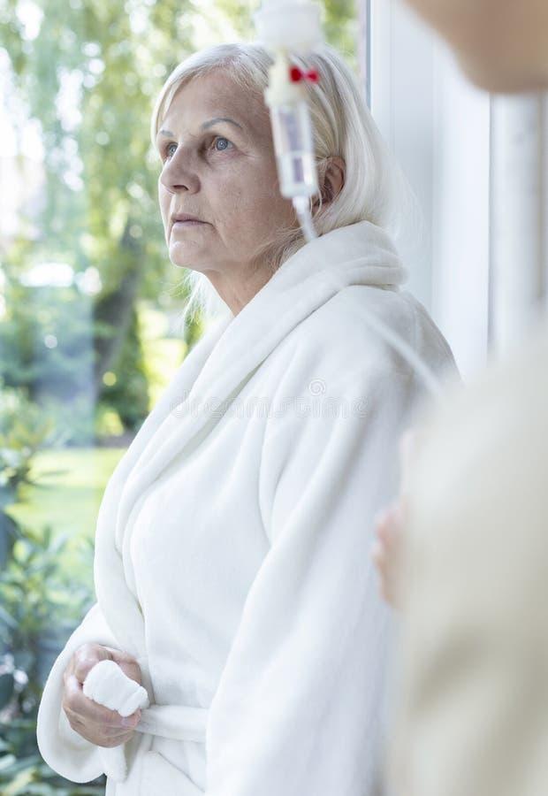 Sad sick senior woman with cancer during chemotherapy in a nursing house. Sad sick senior women with cancer during chemotherapy in a nursing house concept stock photos