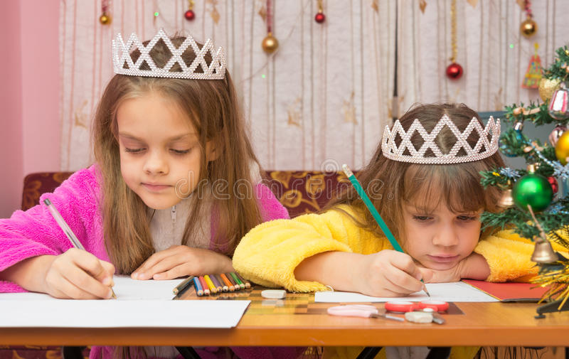 Sad Sisters write letter to Santa Claus royalty free stock images