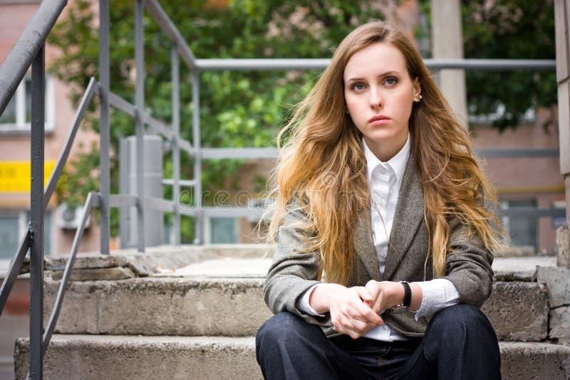 SAD sitter trappuppgångkvinnan royaltyfri foto