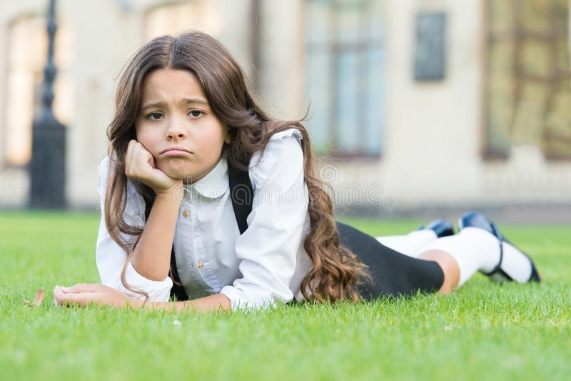 Sad without a smile. Sad schoolgirl relax on green grass. Adorable little child with sad emotion on face. Feeling sad royalty free stock photography