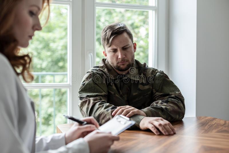 Sad soldier with depression and war syndrome during therapy with psychiatrist. Concept stock image