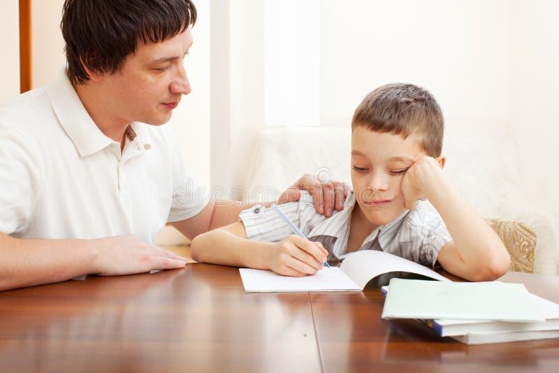Sad son do homework. Father helping son do homework. Problems with homework stock image
