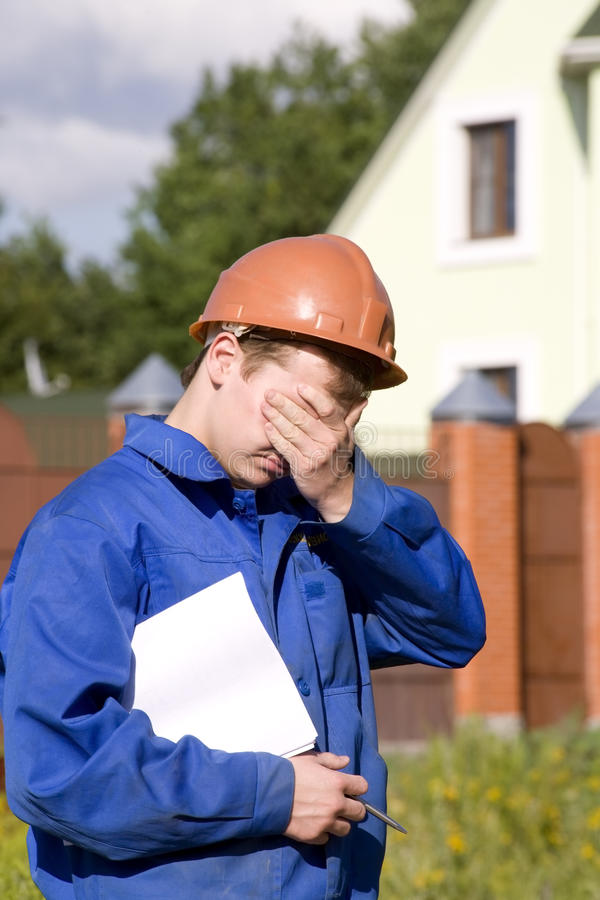 In a sad state working man in the helmet stock photo