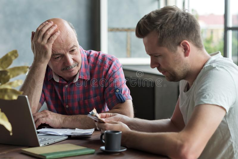 Elderly father and his adult son counting money. Have troubles with taxes and debts stock photo