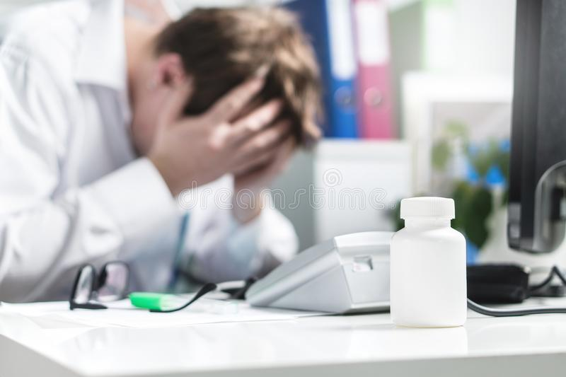 Sad, stressed, upset and unhappy doctor cover face in hospital stock images