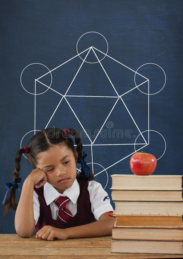 Sad student girl at table against blue blackboard with school and education graphic stock images