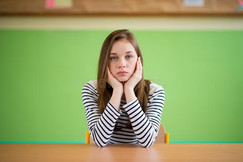 Sad student sitting in classroom with her head in hands. Education, high school, bullying, pressure, depression. royalty free stock image