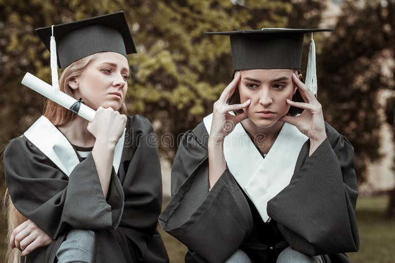 Sad student sitting near her group mate stock photography