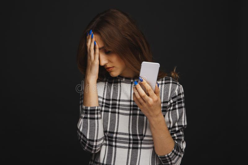 Sad teen being victim of cyber bullying online sitting on a couch in the living room at royalty free stock image