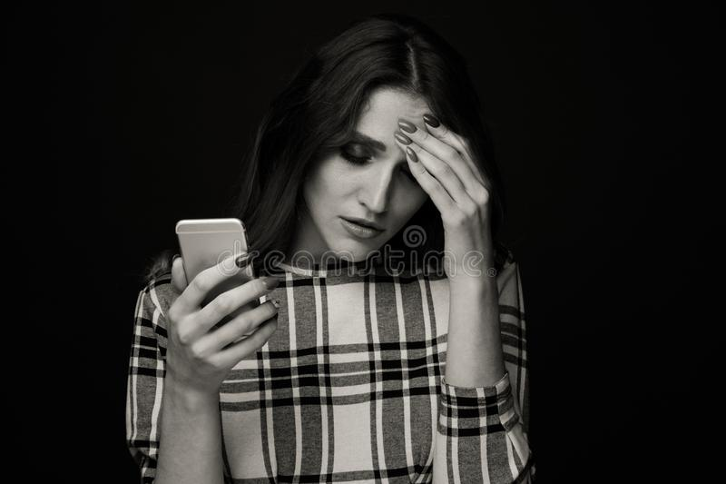 Sad teen being victim of cyber bullying online sitting on a couch in the living room at royalty free stock photo