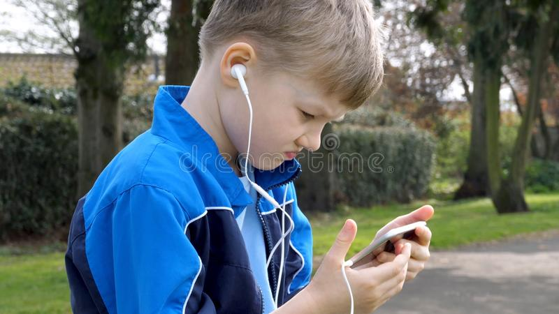 Sad teen boy with smart phone listening or talking while sitting in british park. teenager and social media concept.  royalty free stock image