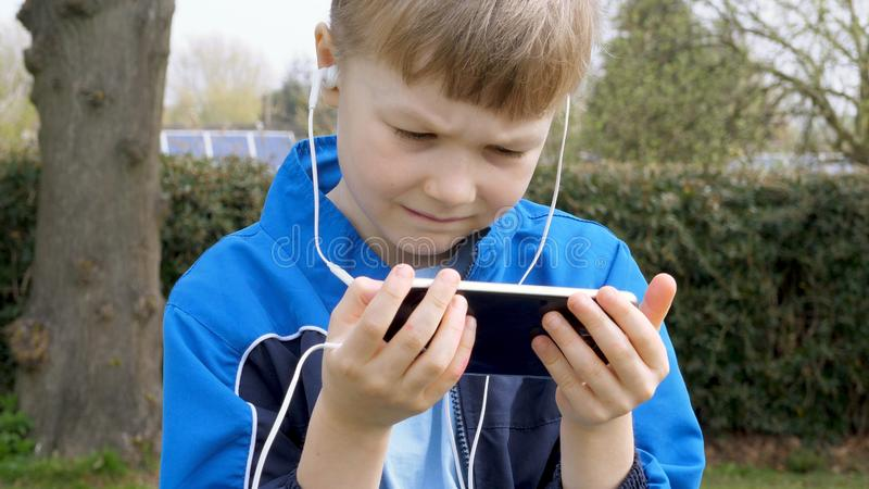 Sad teen boy with smart phone listening or talking while sitting in british park. teenager and social media concept.  stock photo