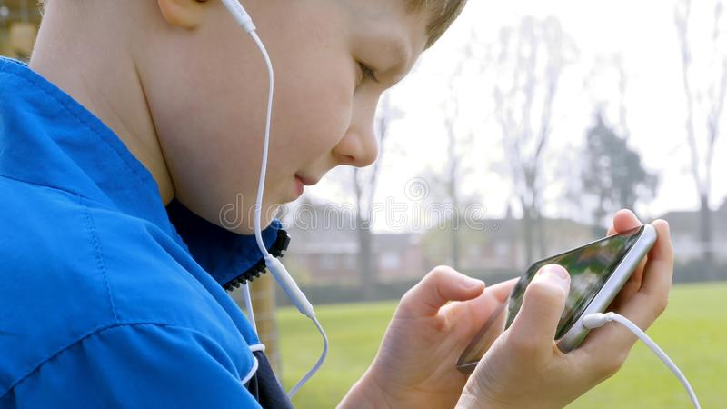 Sad teen boy with smart phone listening or talking while sitting in british park. teenager and social media concept.  royalty free stock images