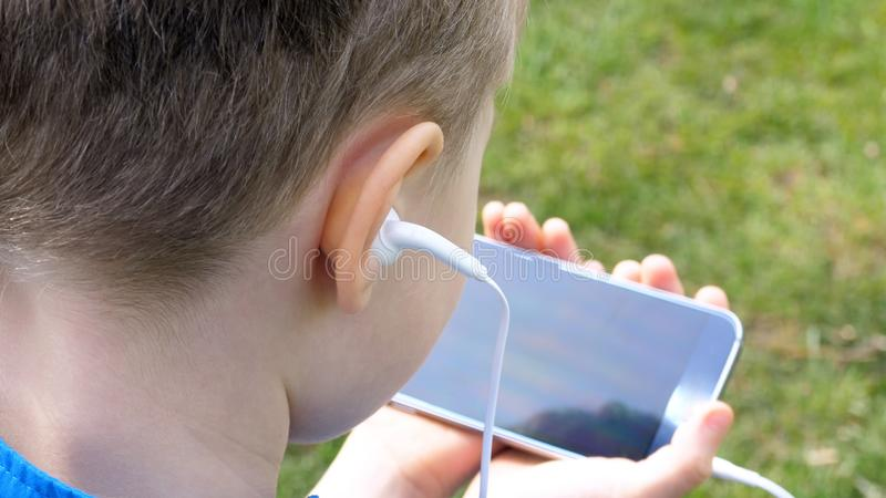 Sad teen boy with smart phone listening or talking while sitting in british park. teenager and social media concept.  royalty free stock photography