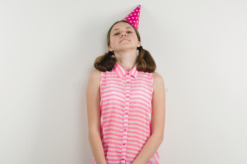 Sad teen girl in festive hat stands alone beside a white wall. Sad teen girl in a festive hat stands alone beside a white wall royalty free stock image