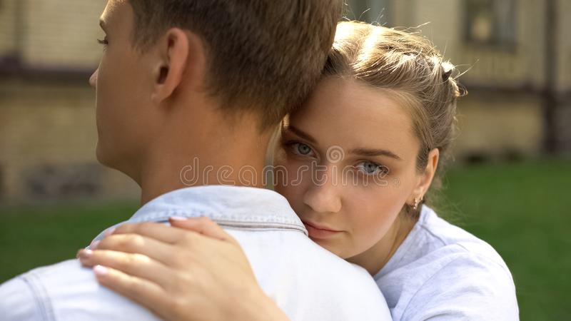 Sad teen girlfriend hugging boyfriend and looks at camera, relation difficulties. Stock photo stock photography