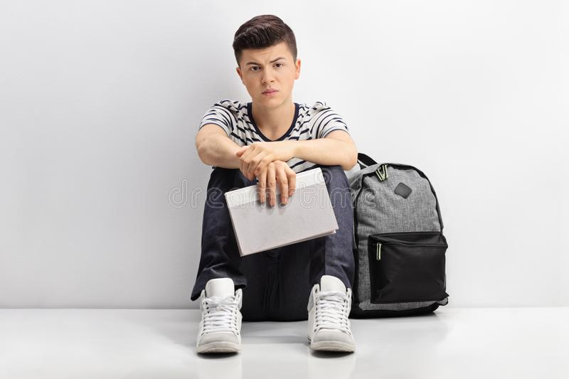 Sad teen student leaning against a wall royalty free stock photography