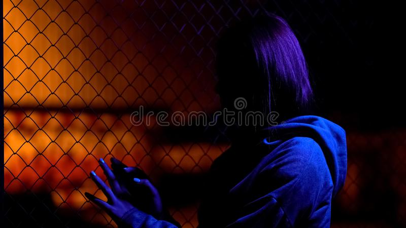 Sad teenage girl hiding near wire fence, family relationship crisis, awkward age royalty free stock images