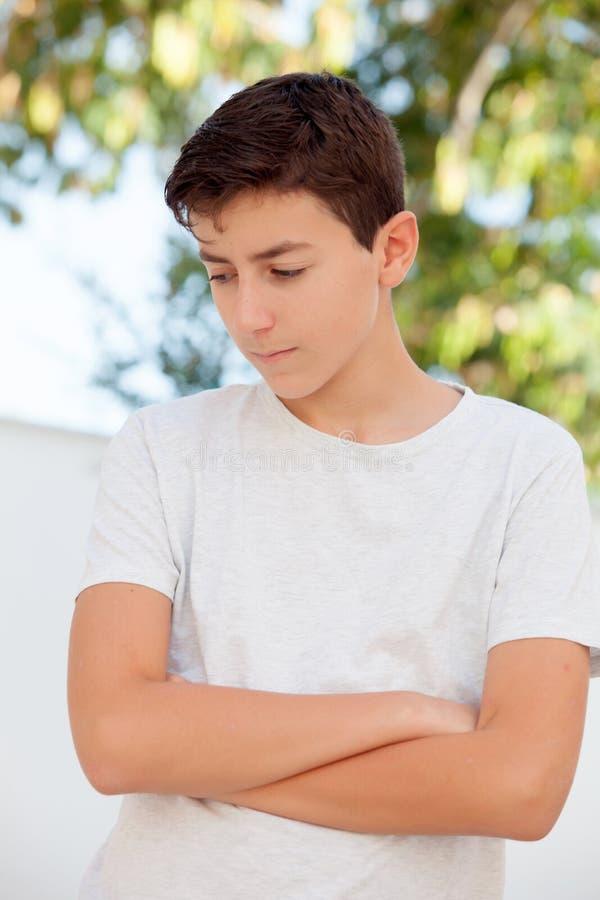Sad teenager boy looking down outdoor stock photo