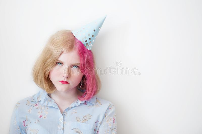 Sad teenager girl in birthday hat stock photo