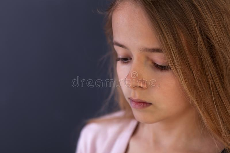 Sad teenager girl portrait. Sad teenager girl looking down - side view portrait, shallow depth royalty free stock images