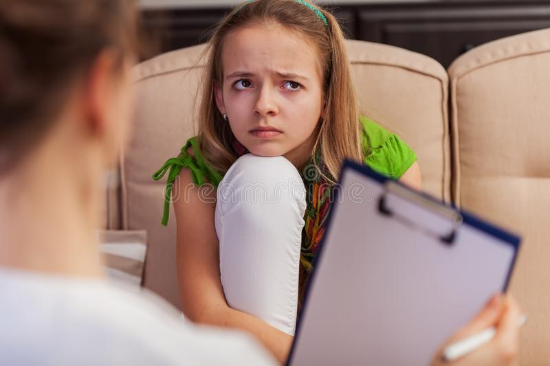 Sad teenager girl seeking help and advice from a counseling professional stock image