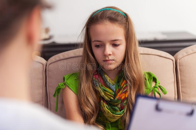 Sad teenager girl seeking help from professional counseling royalty free stock photo