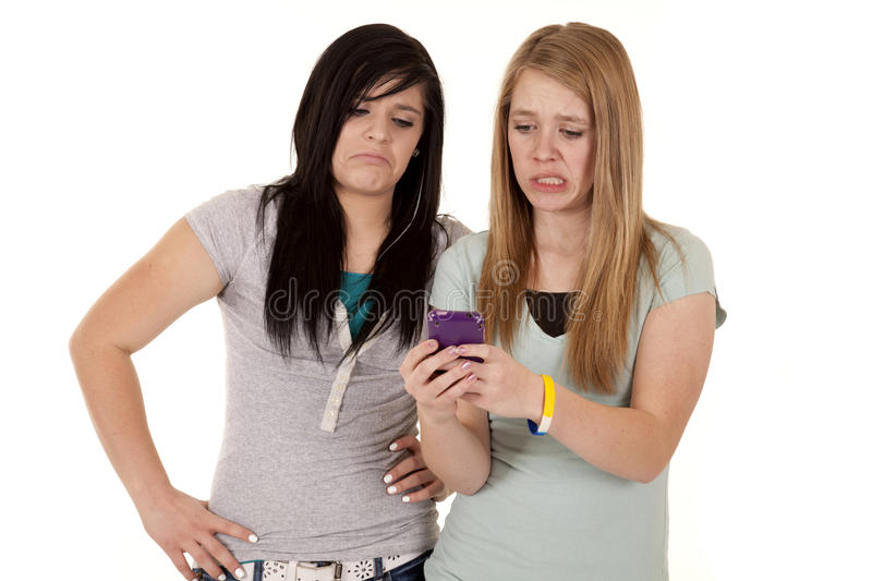 Sad text. A teen girl not getting a good text from someone, her friend feels bad for her stock photo