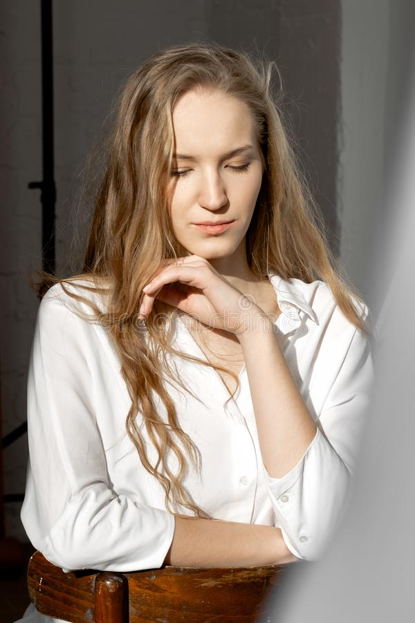 Sad thoughtful model looking down in white shirt stock photography