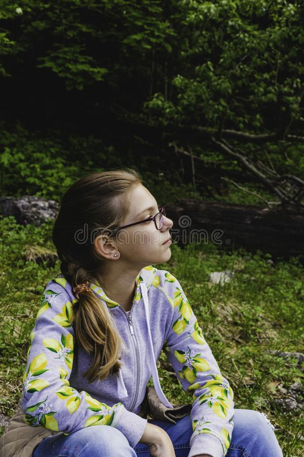 Sad thoughtful teen girl with glasses sitting in the forest on the nature alone. royalty free stock photography