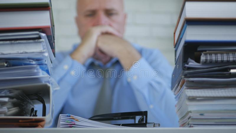 Businessman Image Staying Tired Bored and Upset in Office Room. Sad and Tired Businessperson Image Staying Tired Bored and Upset in Office Room royalty free stock photo