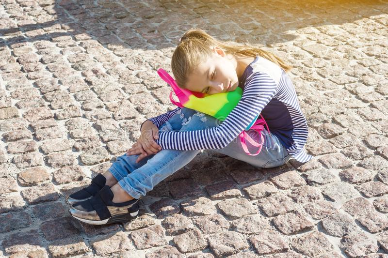 Sad tired child - a girl of 10 years old sits on city pavement stock images