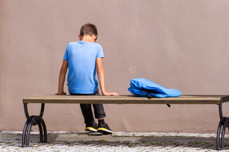 Sad, tired child sitting alone on the bench outdoors. royalty free stock images