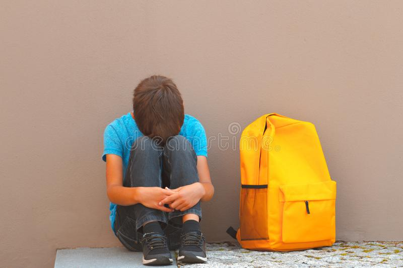Sad, tired child sitting alone on the ground outdoors.  royalty free stock images