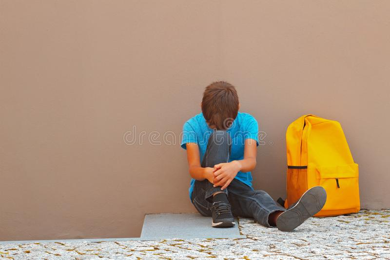 Sad, tired child sitting alone on the ground outdoors.  stock photography