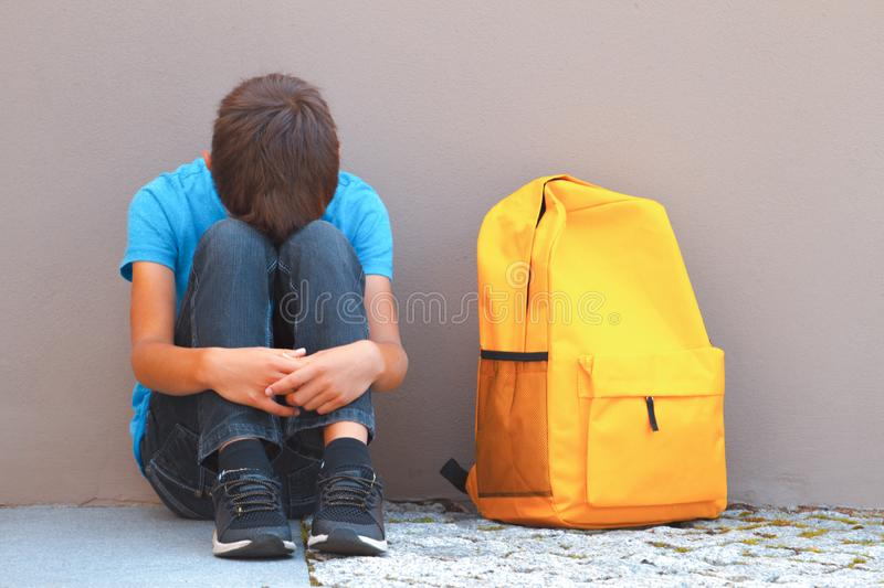 Sad, tired child sitting alone on the ground outdoors.  royalty free stock photo