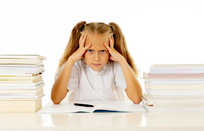 Sad and tired cute schoolgirl with blond hair sitting in stress doing homework overwhelm with too much study and textbooks in. Children education academic royalty free stock photography