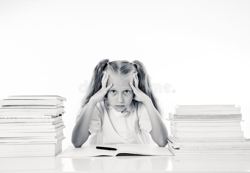 Sad and tired cute schoolgirl with blond hair sitting in stress doing homework overwhelm with too much study and textbooks in. Children education academic stock images