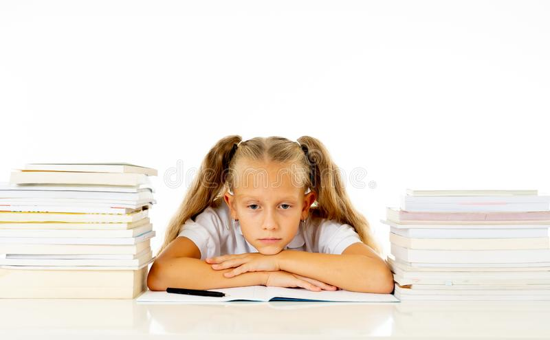 Sad and tired cute schoolgirl with blond hair sitting in stress doing homework overwhelm with too much study and textbooks in. Children education academic stock image