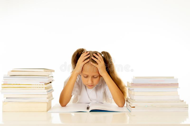Sad and tired cute schoolgirl with blond hair sitting in stress doing homework overwhelm with too much study and textbooks in. Children education academic royalty free stock images