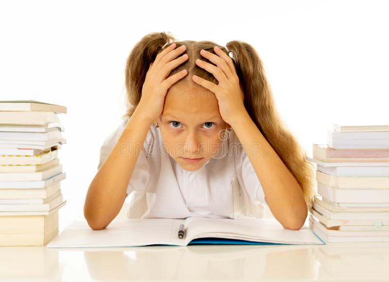 Sad and tired cute schoolgirl with blond hair sitting in stress doing homework overwhelm with too much study and textbooks in. Children education academic royalty free stock photo