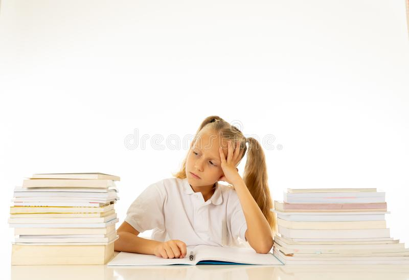 Sad and tired cute schoolgirl with blond hair sitting in stress doing homework overwhelm with too much study and textbooks in. Children education academic stock photography