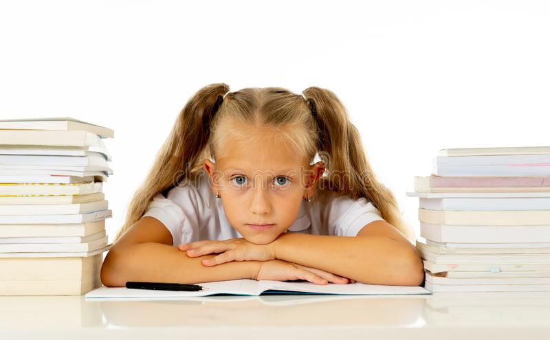 Sad and tired cute schoolgirl with blond hair sitting in stress doing homework overwhelm with too much study and textbooks in. Children education academic royalty free stock image
