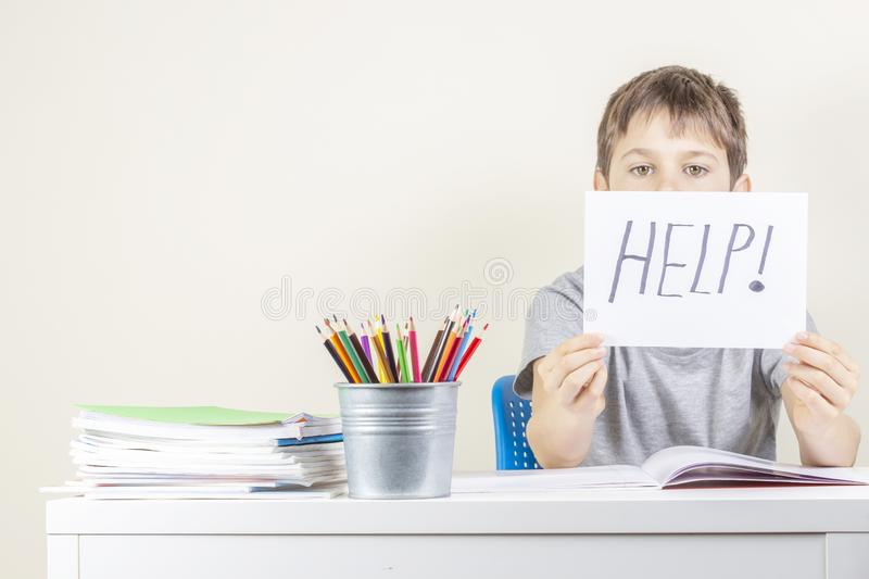 Sad tired frustrated boy sitting at the table with many books and holding paper with word Help. Learning difficulties stock images